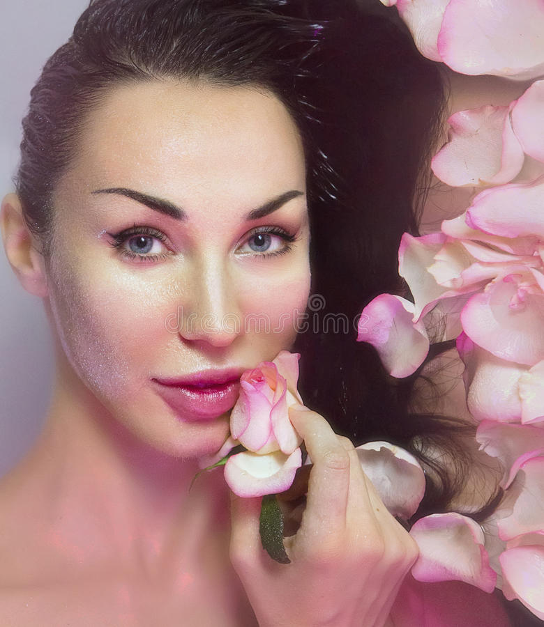 Woman with Fresh Rose petals and pink rosebud. Natural Rose water. Woman with clean Healthy skin. Fresh Rose petals and pink rosebud. Natural Rose water for royalty free stock photography