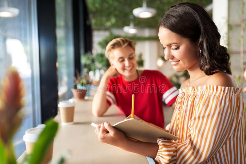Woman with friend at cafe writing to notebook royalty free stock photos