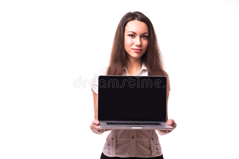 Woman with friendly happy smile holding a laptop computer. Smiling pretty young woman with friendly happy smile holding a laptop computer and pointing at screen royalty free stock image
