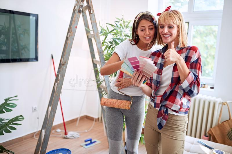 Woman friends choosing the right color for new home stock images