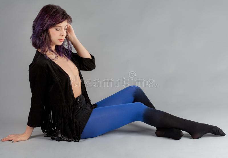 Woman in Fringe Jacket and Ombre Stockings. An image of a pretty seated young woman in black fringed jacket and blue to black ombre tights royalty free stock images