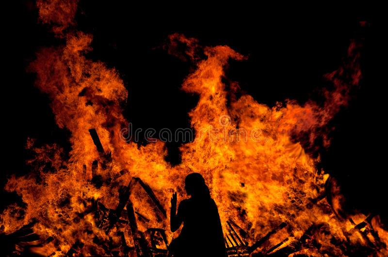 Woman in front of a big fire. Woman standing in front of a big fire royalty free stock photography