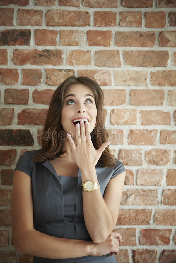 Woman in front of brick wall royalty free stock photos