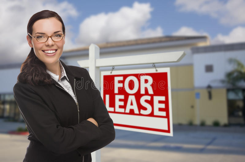 Woman In Front of Commercial Building and For Lease Sign royalty free stock photo