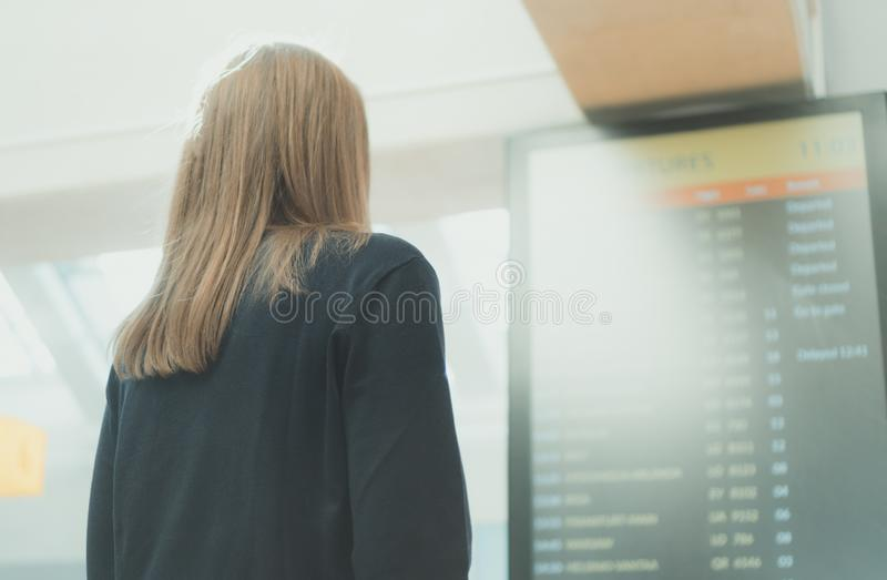 Woman checking her flight. Woman in front of flight information board, checking her flight royalty free stock images