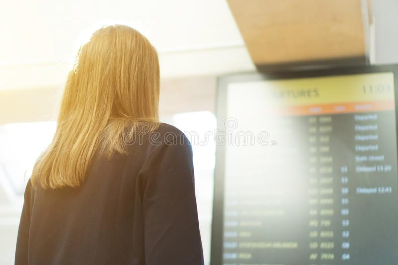 Woman checking her flight. Woman in front of flight information board, checking her flight stock photo