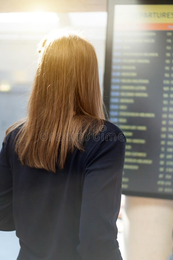 Woman checking her flight. Woman in front of flight information board, checking her flight royalty free stock image