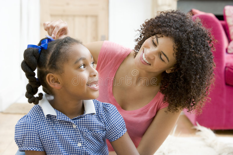 Woman in front hallway fixing young girl's hair an stock image