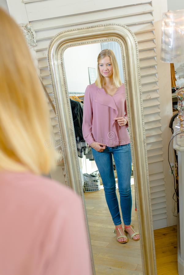 Woman in front mirror royalty free stock photography