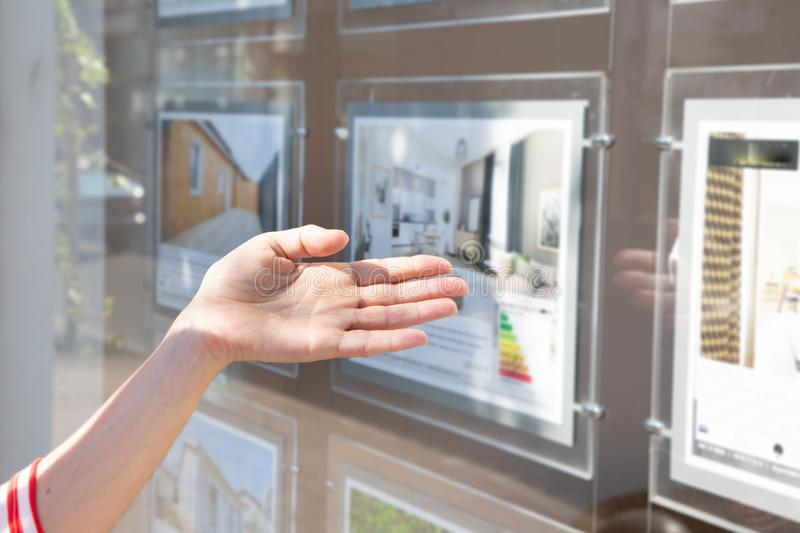 Woman in front of real estate agent showcase window. A woman in front of real estate agent showcase window stock photography