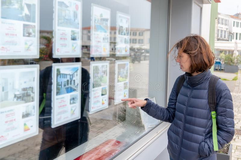 Woman in front of shop real estate agency. A woman in front of shop real estate agency royalty free stock image