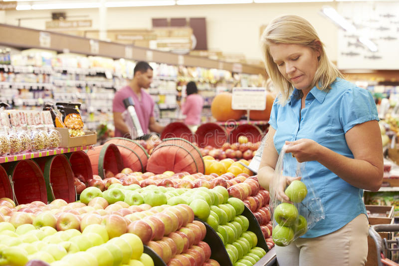 Woman At Fruit Counter In Supermarket stock photo