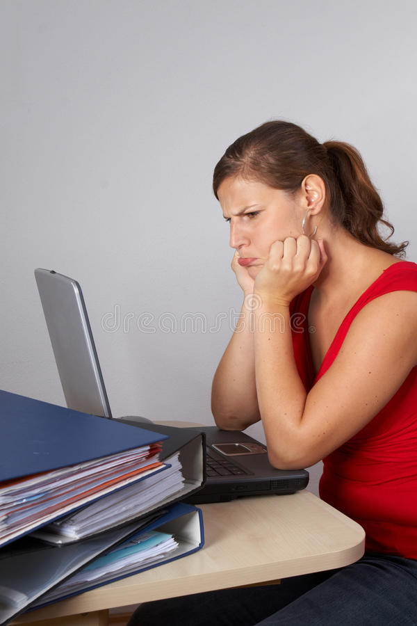 Woman in frustration. Young woman sitting at her laptop with a lot of work in front of her. She is very frustrated stock image
