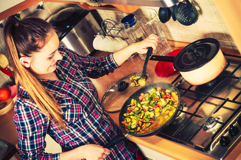 Woman frying frozen vegetables. Stir fry. Woman in kitchen cooking stir fry frozen vegetables. Girl frying making delicious dinner food meal. Instagram filtered royalty free stock photo