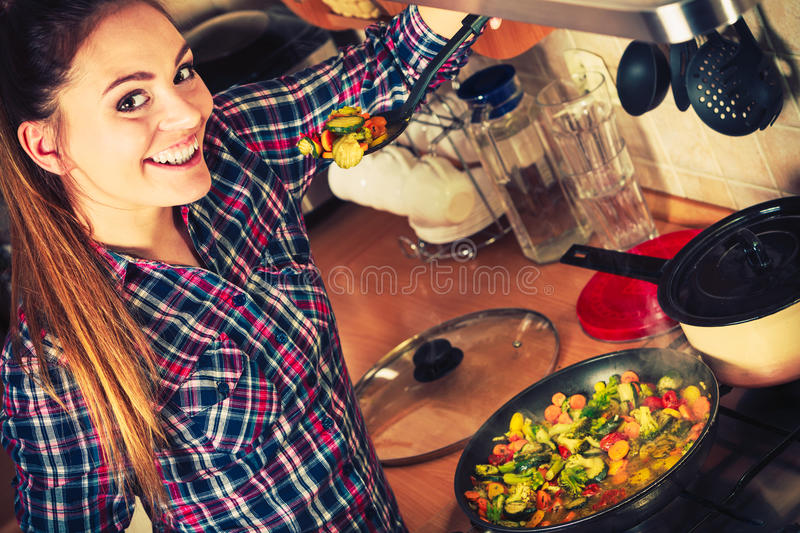 Woman frying frozen vegetables. Stir fry. stock photography