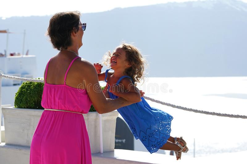 Woman with fuchsia dress plays with her little daughter on Oia Scenery as a background in Santorini royalty free stock photo