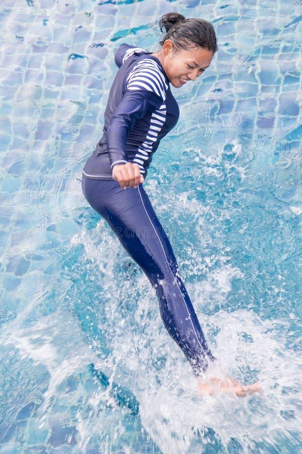 Woman in full body swimsuit doing kicks in the swim pool. stock images