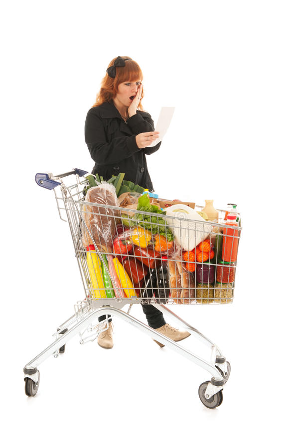 Woman with full shopping cart reading receipt. Critical costumer reading receipt from groceries in supermarket stock images