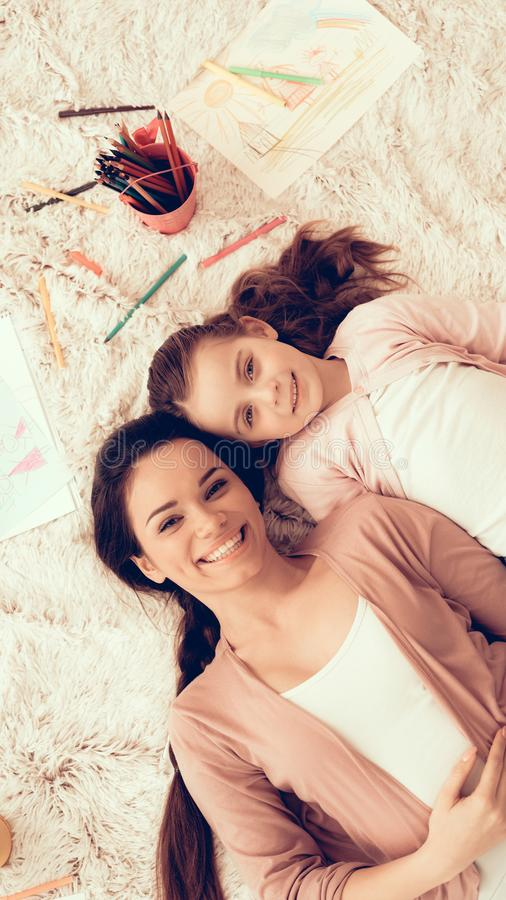Woman and Girl Lie on White Carpet with Pencils stock images