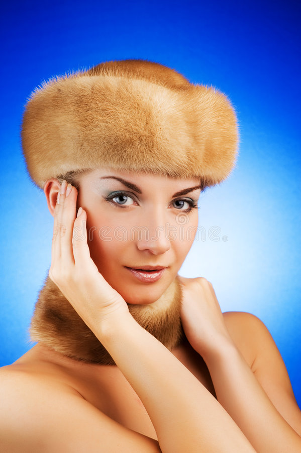 Woman in fur cap. Beautiful young woman in fur cap royalty free stock images