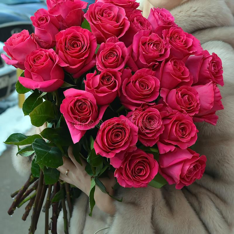 The woman in a fur coat with a huge bouquet of roses. royalty free stock photography