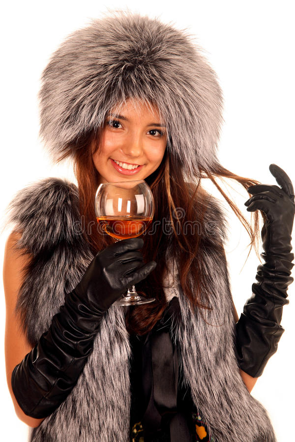 Woman in a fur coat keeps glass and smile stock photography