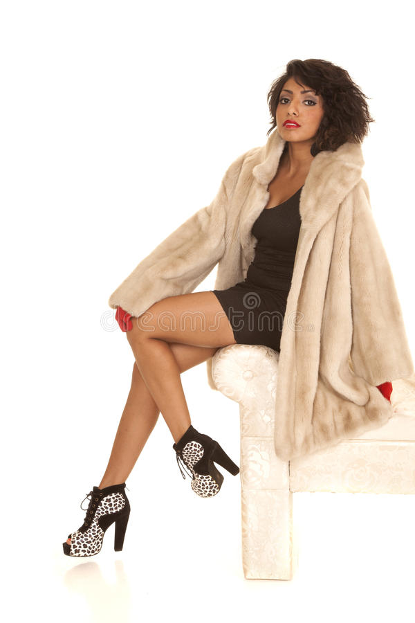 Woman fur coat legs sit serious royalty free stock photos