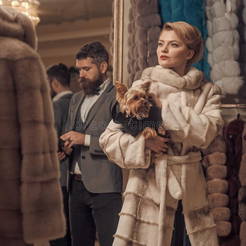 Woman in fur coat with man, shopping, seller and customer. Date, couple, love, men and woman. Couple in love among fur coat with dog, luxury. Fashion and stock photo