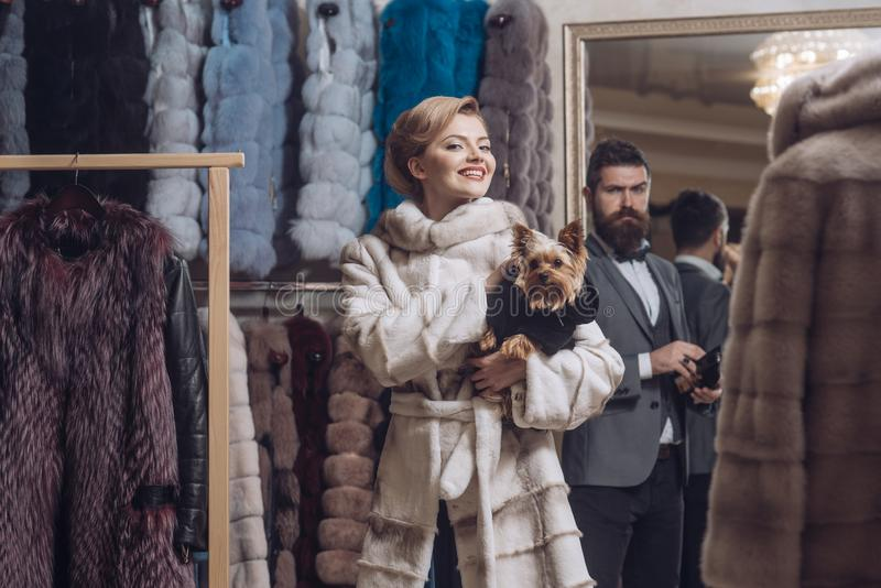 Woman in fur coat with man, shopping, seller and customer. Fashion and beauty, winter. Couple in love among fur coat with dog, luxury. Purchase, business stock images