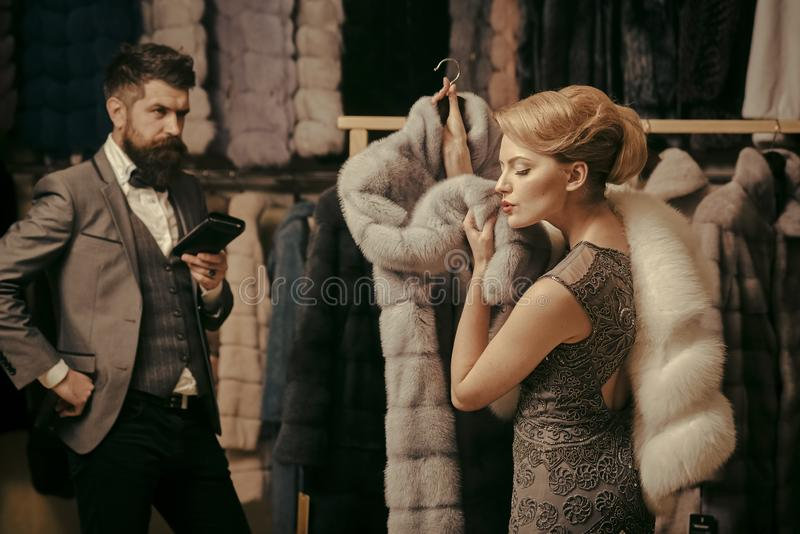 Woman in fur coat with man, shopping, seller and customer. stock photography