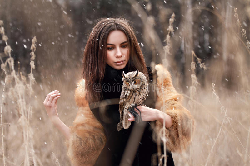 Woman in fur coat with owl on hand by first autumn snow. Beautiful brunette with long hair in nature, holding an owl. Romantic, d stock photo