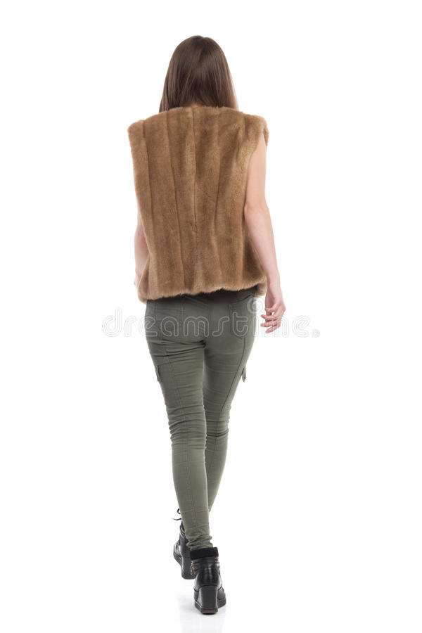 Woman In Fur Waistcoat Walking Rear View. Young woman in brown fur waistcoat, khaki pants and black boots is walking. Rear view. Full length studio shot on white royalty free stock photo