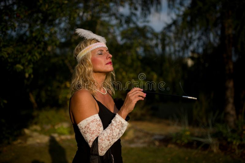 Woman in the garden - 1930s style. Nice woman in the garden, late afternoon. Dress code year 1930 - dress style royalty free stock photo