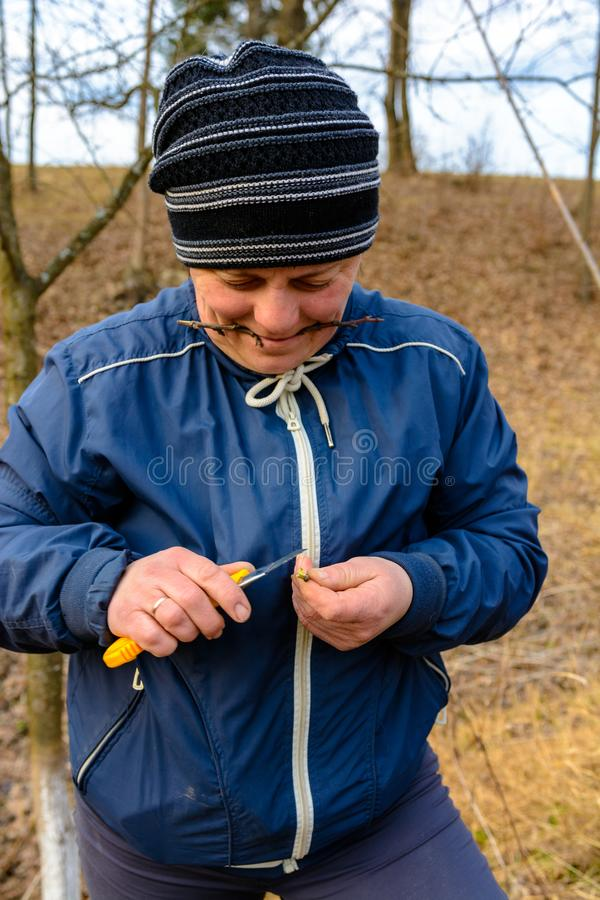 A woman gardener cuts a clip of wood for vaccination with a sharp knife royalty free stock photography