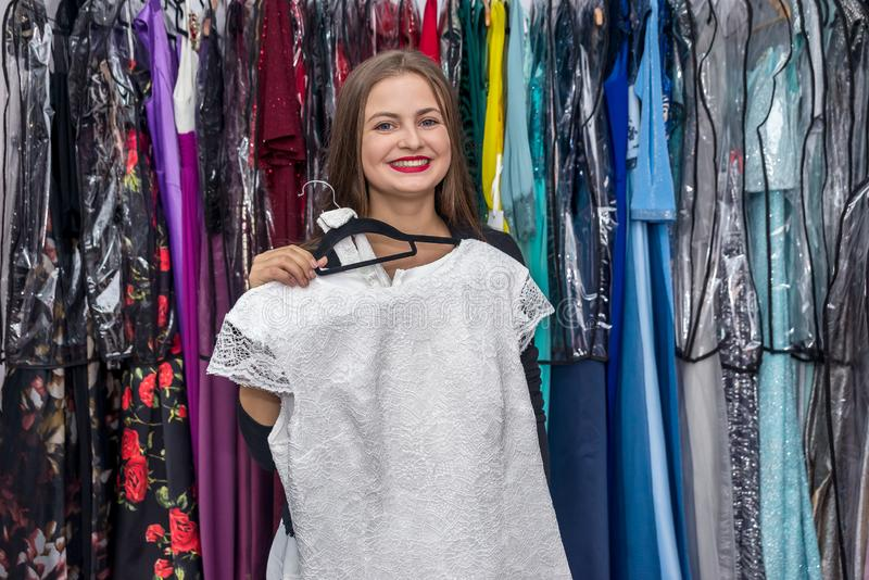 Woman in garment store trying on beautiful dress royalty free stock photo