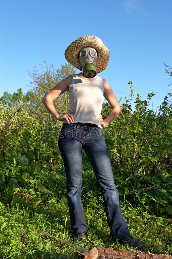 Woman in gas-mask at garden work stock image