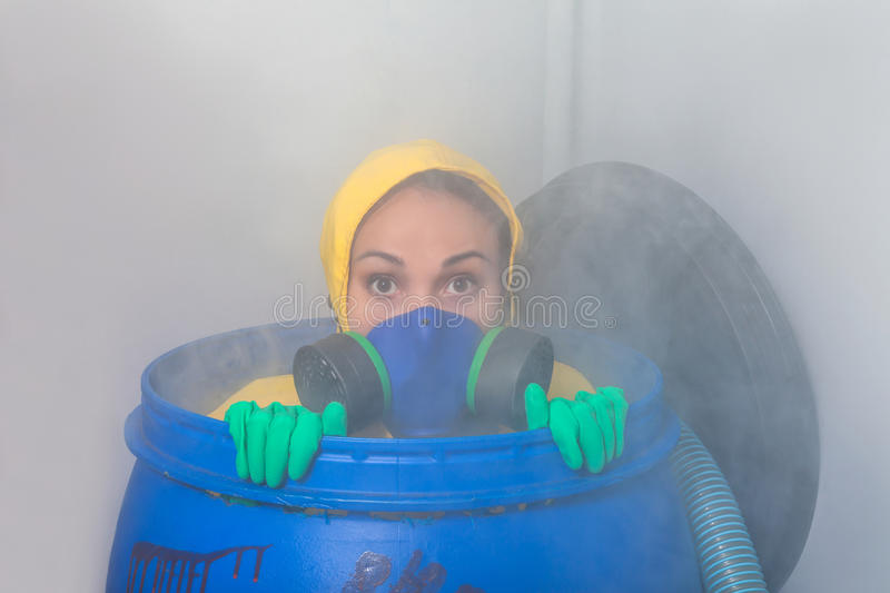 Woman in gas mask. Sitting in the barrel stock photo