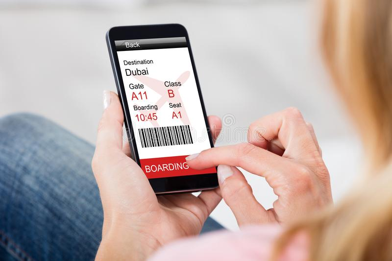 Woman Generating Boarding Pass On Smart Phone At Home royalty free stock photos