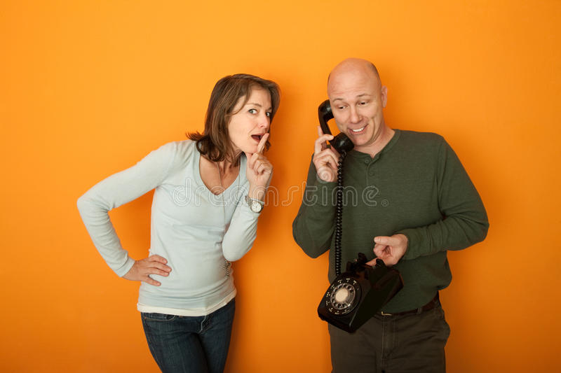 Woman Gestures To Be Silent. While man is on telephone conversation stock images