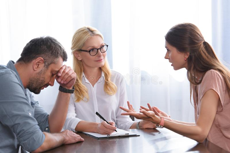 Woman gesturing by hands and quarreling with stressed husband sitting with hand on forehead at table on therapy session by female. Counselor in office stock images