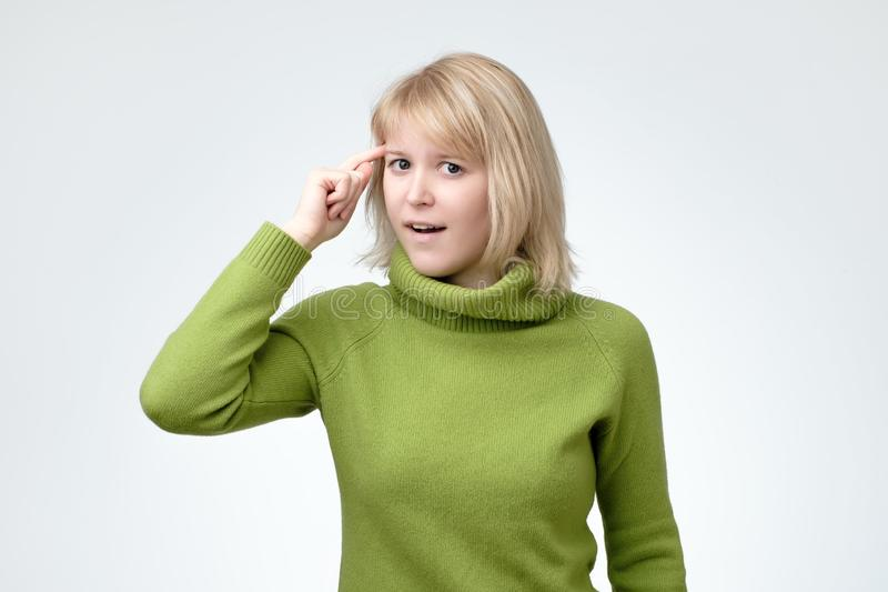 Woman gesturing, twisting her index finger at temple, asking to think carefully. Blonde smiling young woman dressed in green sweater gesturing, twisting her royalty free stock image