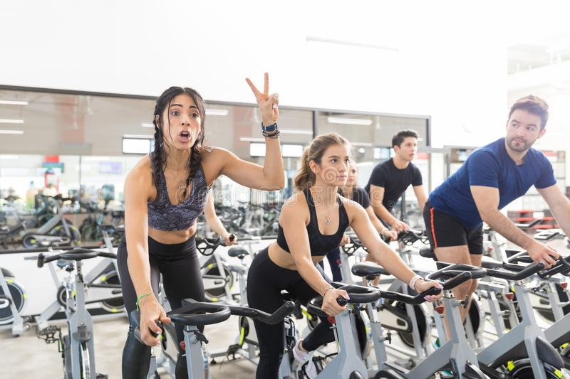 Woman Gesturing Victory While Exercising On Spinning Bike In Gym royalty free stock images