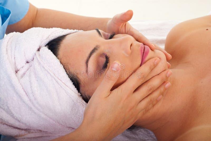 Woman get facial massage at spa stock images