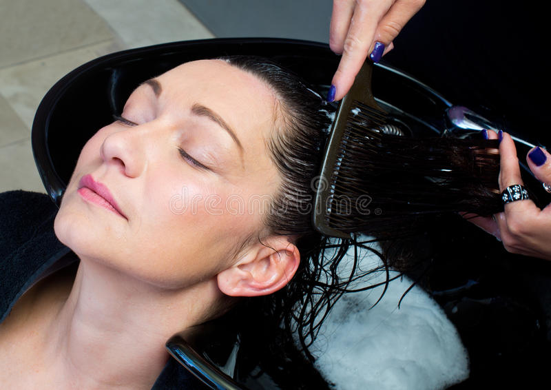 Woman get hair washing and combing stock image