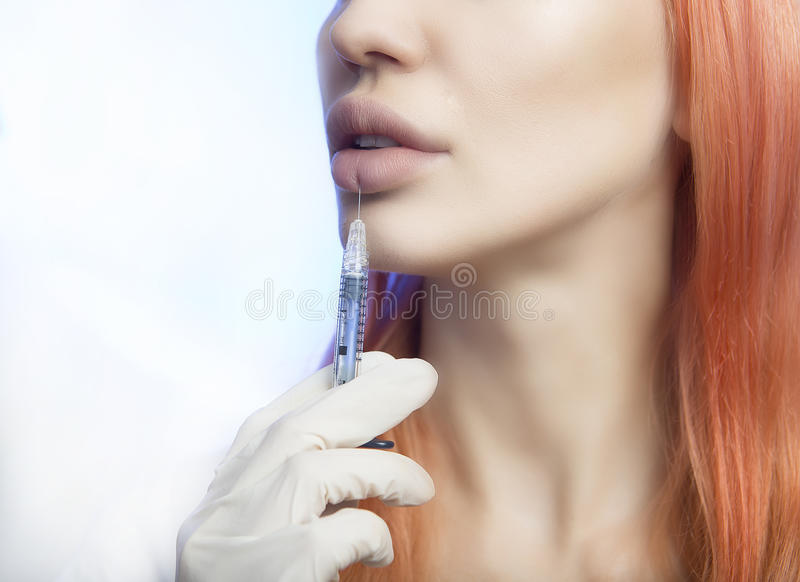 Woman Geting an Injection in her Lips in Beauty Salon. Young Woman Geting an Injection in her Lips. Beauty Injections -Woman wondered about methods lip stock photo