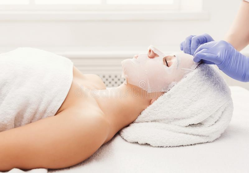 Woman gets face mask by beautician at spa stock images