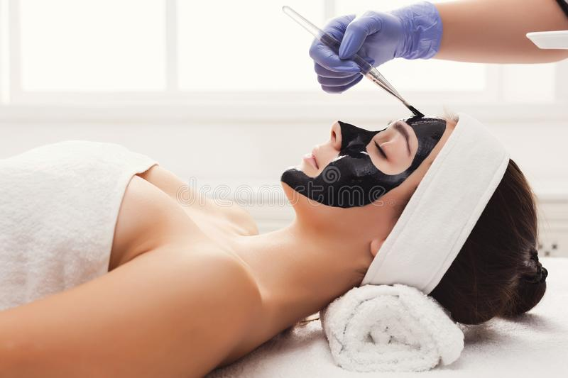 Woman gets face mask by beautician at spa royalty free stock photo