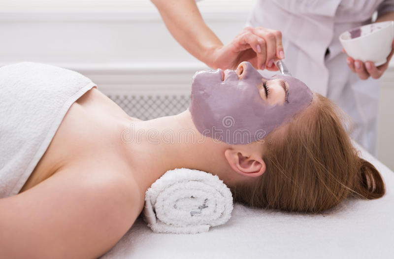 Woman gets face mask by beautician at spa royalty free stock image