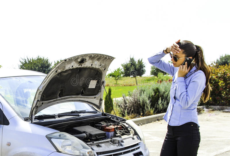 A woman with a broken car, talking on the phone, waits for assistance royalty free stock photos