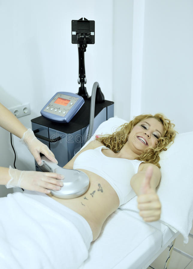 Woman gets therapy treatment at spa salon. Young woman gets slimming treatment at spa salon stock images